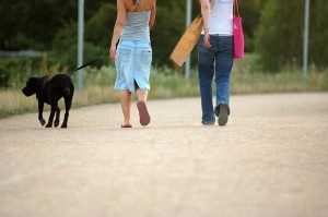 2 women walking a dog